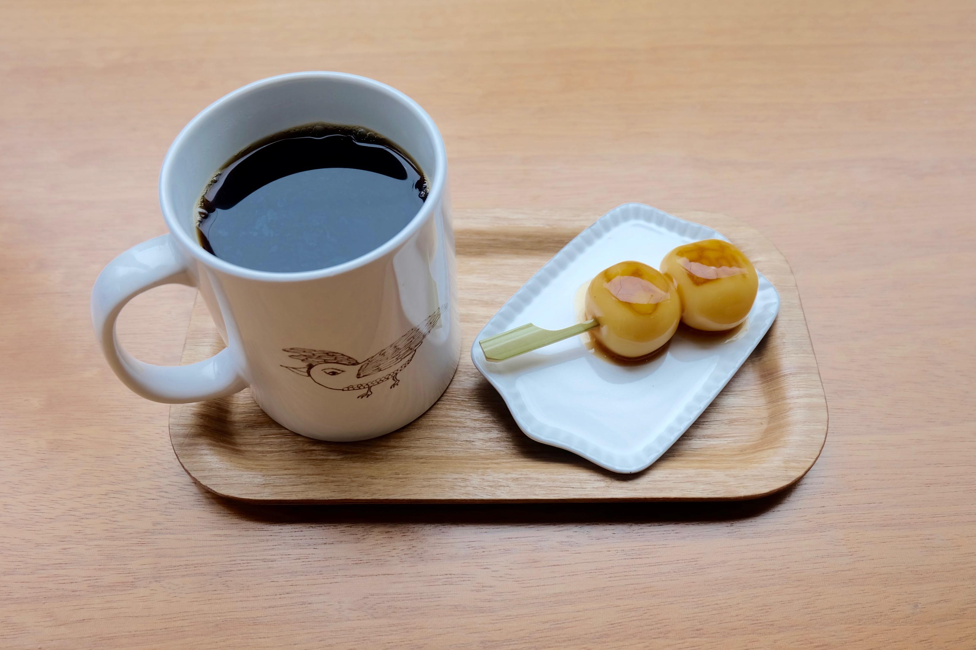 映画でも使用された珈琲「かわせみ」が入ったマグカップにはヨダちゃんのロゴが。お団子には、内藤さんが生み出したイラスト「半吉さん」も。
